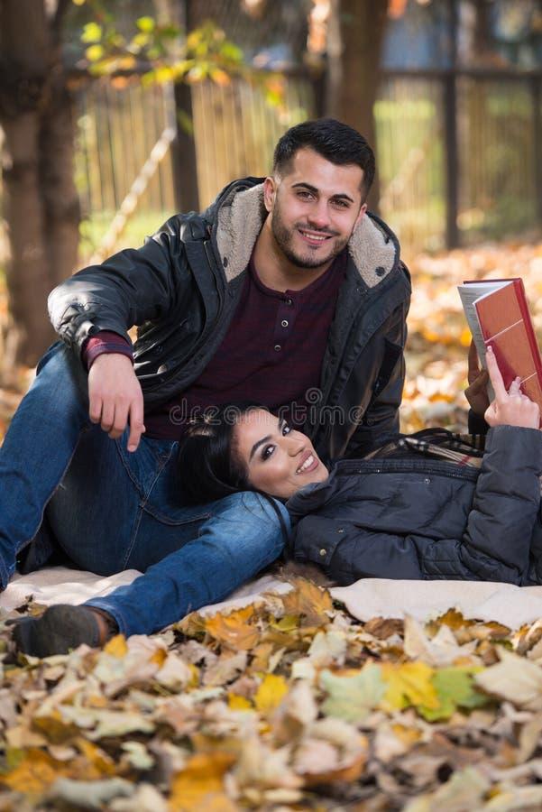 Ζεύγος που διαβάζει ένα βιβλίο κατά τη διάρκεια του φθινοπώρου στοκ φωτογραφίες