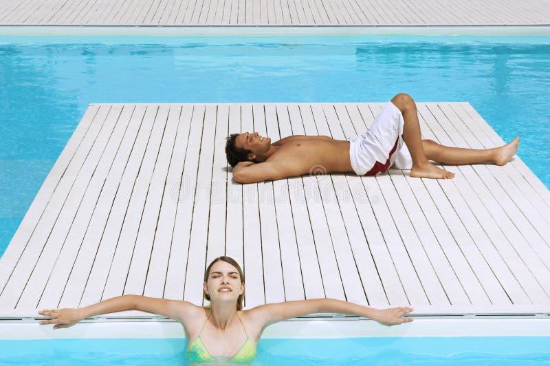 Ζεύγος που κάνει ηλιοθεραπεία σε Poolside στοκ φωτογραφία