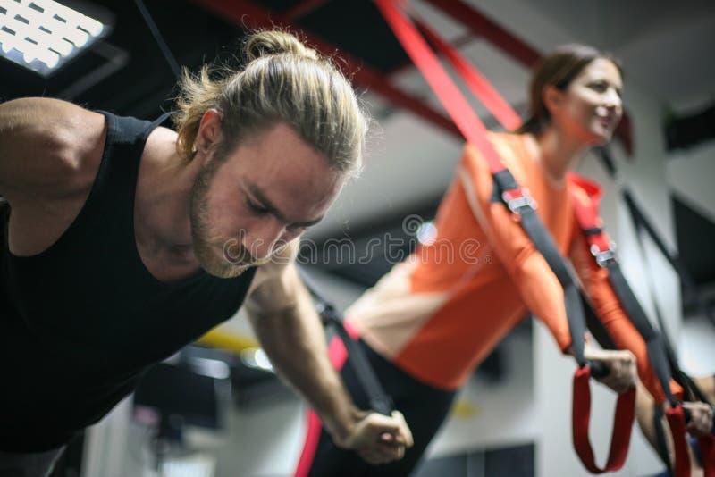 Ζεύγος που κάνει τις ασκήσεις σε μια γυμναστική με τα λουριά στοκ εικόνες