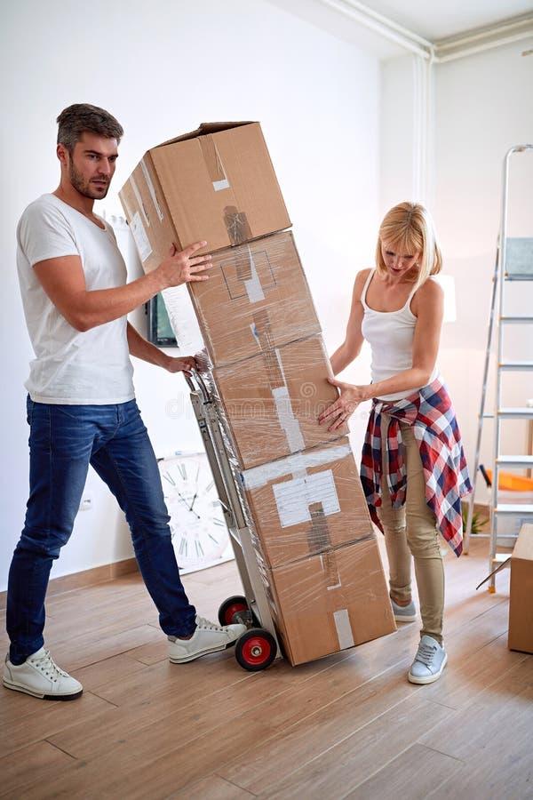 Ζεύγος που κινείται στο νέο σπίτι Άνδρας και γυναίκα με τα κουτιά από χαρτόνι κινούμενη στο εσωτερικό στοκ εικόνα