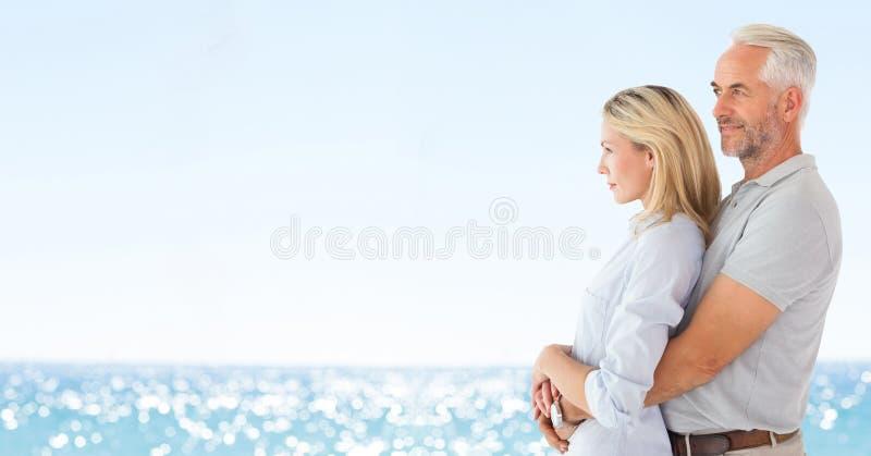 Ζεύγος που κοιτάζει στο αριστερό ενάντια στη μουτζουρωμένη παραλία στοκ φωτογραφίες με δικαίωμα ελεύθερης χρήσης