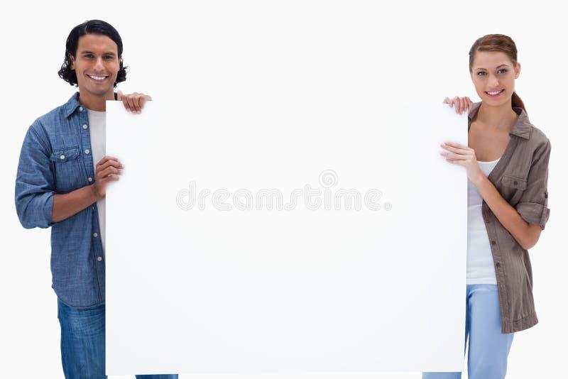 Ζεύγος που κρατά ένα κενό σημάδι στοκ φωτογραφίες