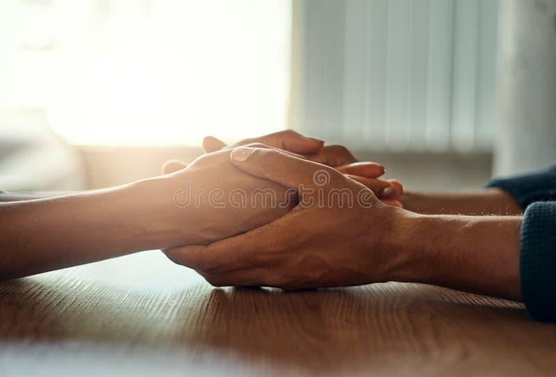 Ζεύγος που κρατά τα χέρια τους στο γραφείο στοκ φωτογραφία