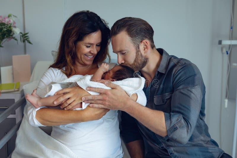 Ζεύγος που κρατά το νεογέννητο μωρό τους στο θάλαμο στοκ εικόνα