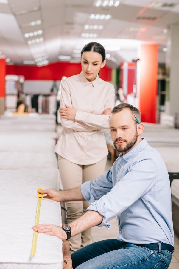 ζεύγος που μετρά το στρώμα με την ταινία μέτρου στο κατάστημα επίπλων στοκ φωτογραφία με δικαίωμα ελεύθερης χρήσης