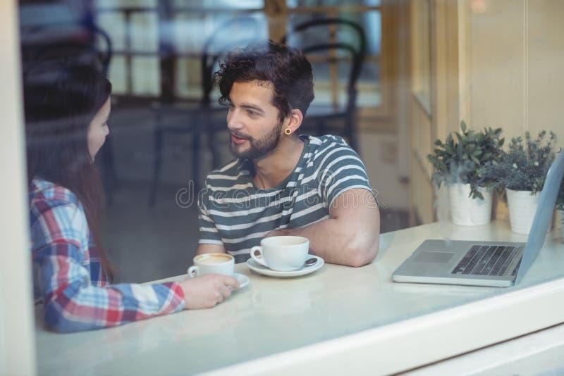 Ζεύγος που μιλά καθμένος από το παράθυρο στον καφέ στοκ εικόνα