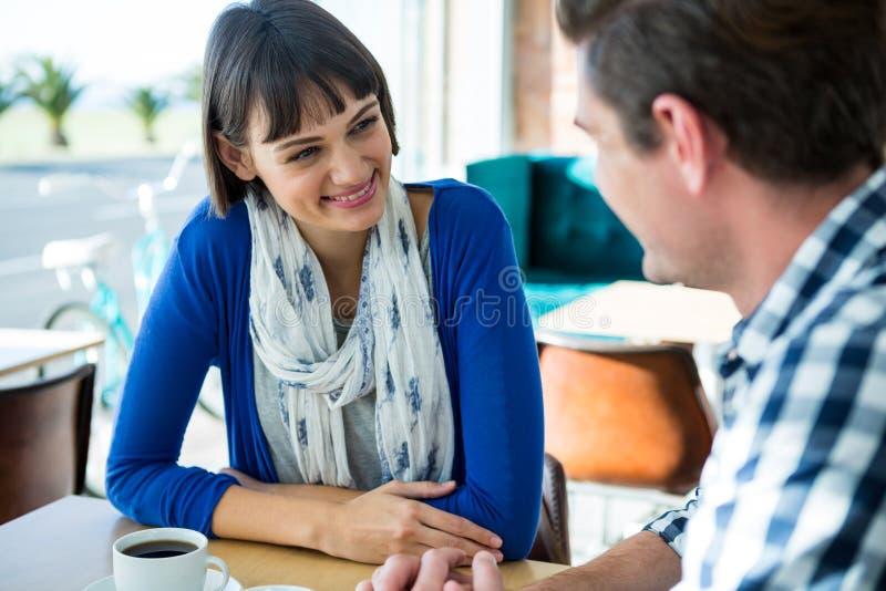 Ζεύγος που μιλά ο ένας στον άλλο στο sho καφέ στοκ εικόνα