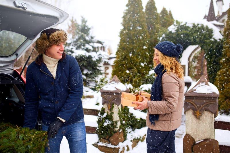 Ζεύγος που ξεφορτώνει τα πρόσφατα περιορίζω? κιβώτια χριστουγεννιάτικων δέντρων και δώρων από τον κορμό αυτοκινήτων για να διακοσ στοκ εικόνες