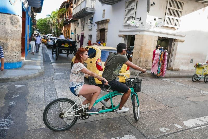 Ζεύγος που οδηγά το διπλό ποδήλατο μέσω των οδών πόλεων, έννοια της μεταφοράς, αναψυχή στοκ φωτογραφία με δικαίωμα ελεύθερης χρήσης
