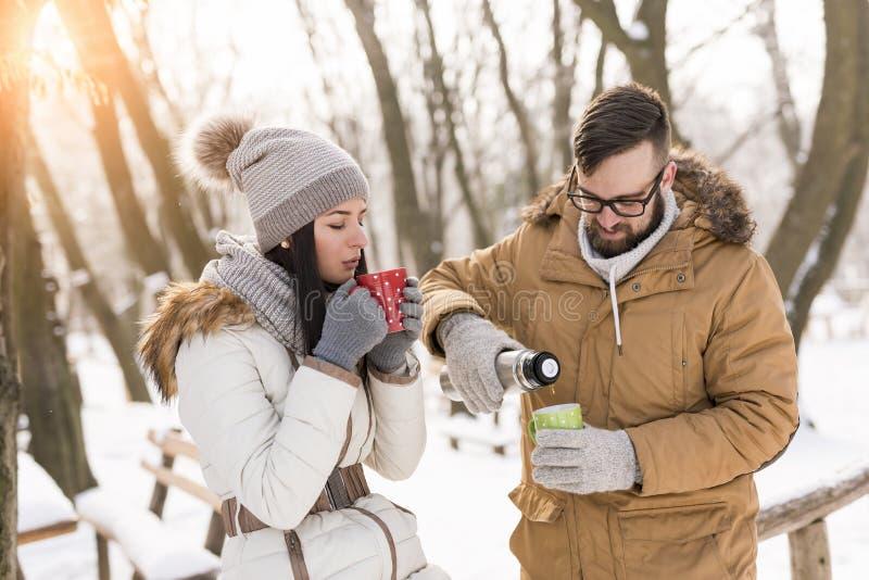 Ζεύγος που πίνει το καυτό τσάι υπαίθρια στο χιόνι στοκ εικόνα με δικαίωμα ελεύθερης χρήσης