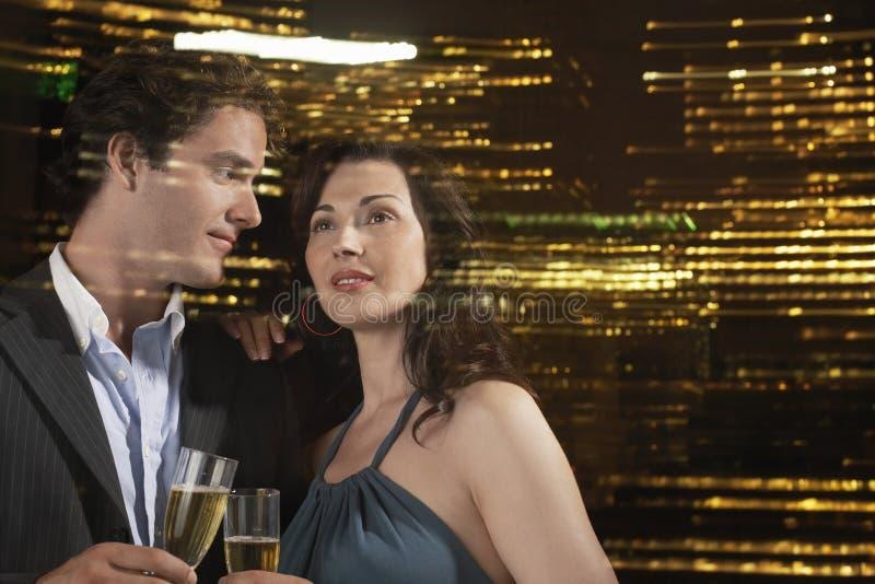 Ζεύγος που πίνει CHAMPAGNE ενάντια στον ορίζοντα νύχτας στοκ φωτογραφίες με δικαίωμα ελεύθερης χρήσης