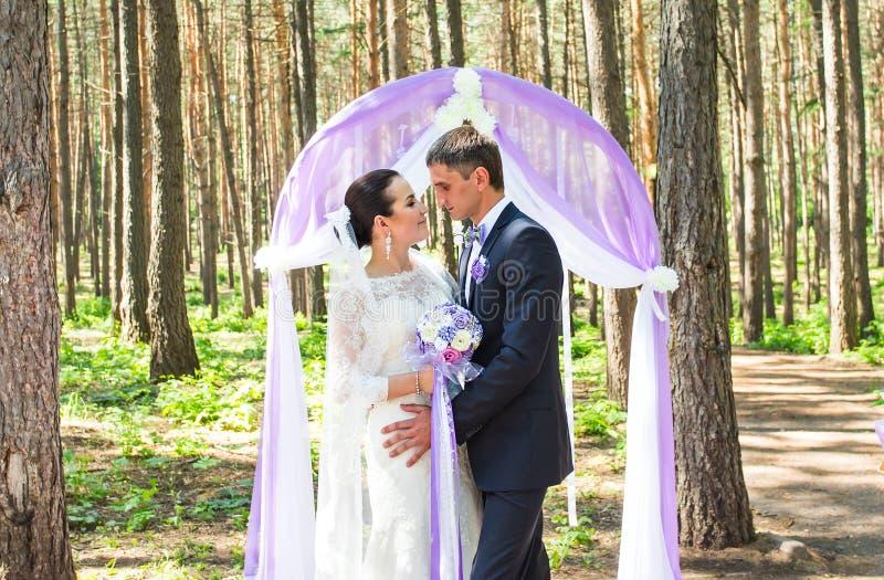 Ζεύγος που παντρεύεται σε μια υπαίθρια γαμήλια τελετή, στοκ εικόνα
