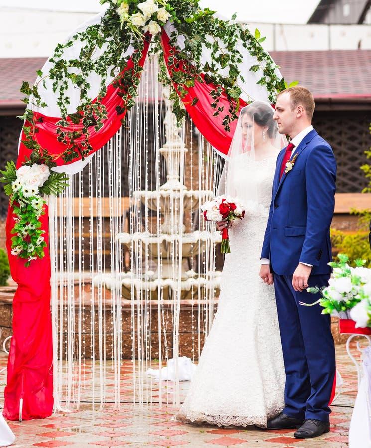 Ζεύγος που παντρεύεται σε μια υπαίθρια γαμήλια τελετή στοκ φωτογραφία