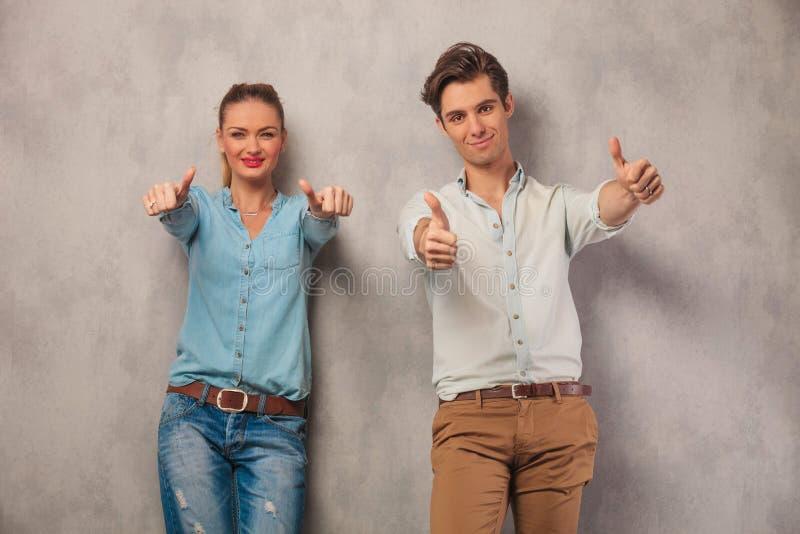 Ζεύγος που παρουσιάζει και τους δύο αντίχειρες στο υπόβαθρο στούντιο στοκ εικόνα με δικαίωμα ελεύθερης χρήσης