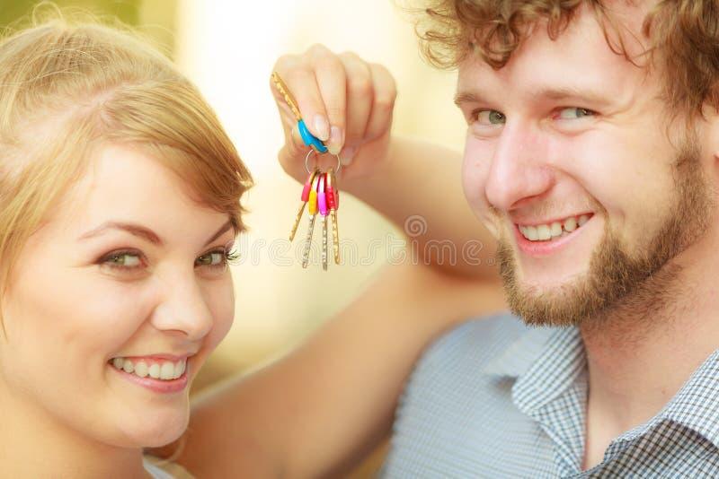Ζεύγος που παρουσιάζει κλειδιά καινούργιων σπιτιών τους στοκ εικόνα με δικαίωμα ελεύθερης χρήσης