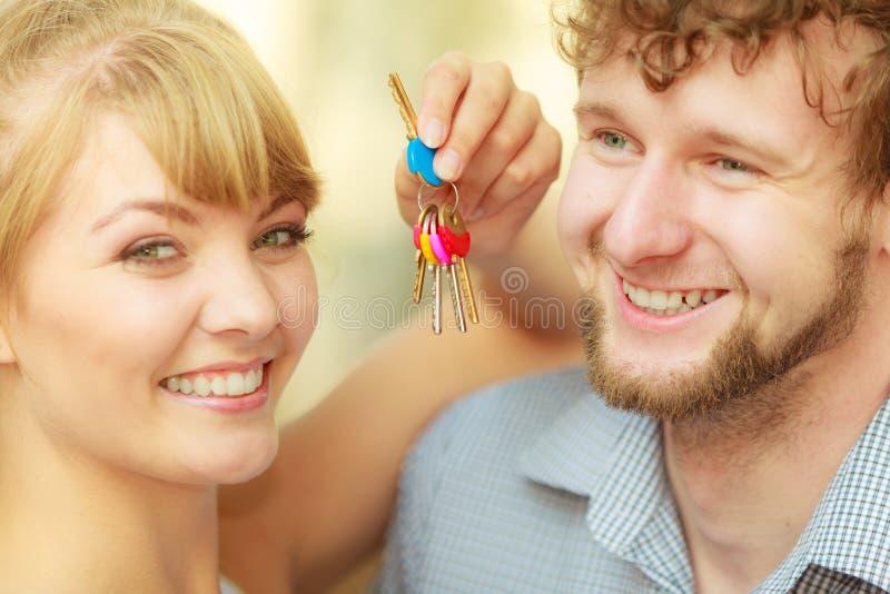 Ζεύγος που παρουσιάζει κλειδιά καινούργιων σπιτιών τους στοκ εικόνα