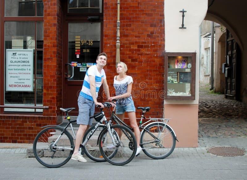 Ζεύγος που περπατά με το ποδήλατο στην παλαιά πόλη, Vilnius στοκ φωτογραφία