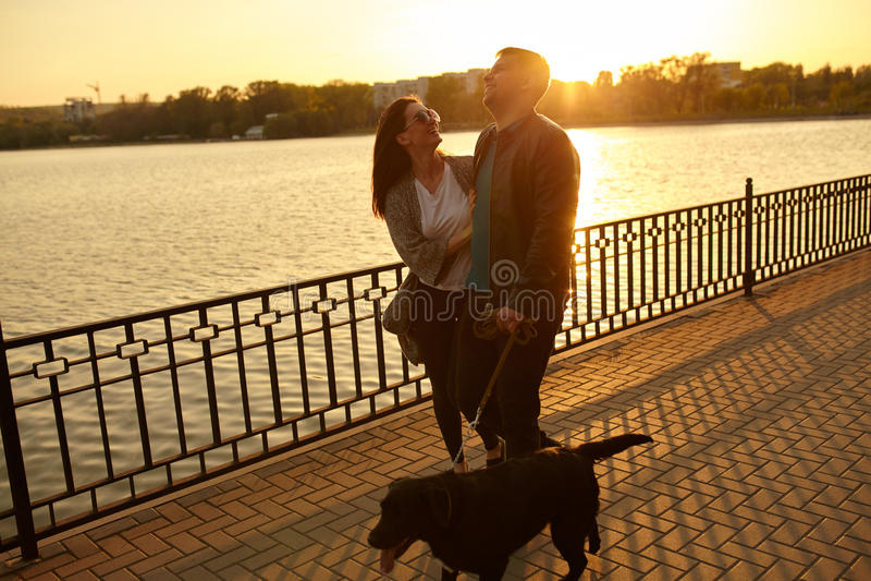 Ζεύγος που περπατά με το σκυλί κατοικίδιων ζώων από τη λίμνη στοκ εικόνες με δικαίωμα ελεύθερης χρήσης