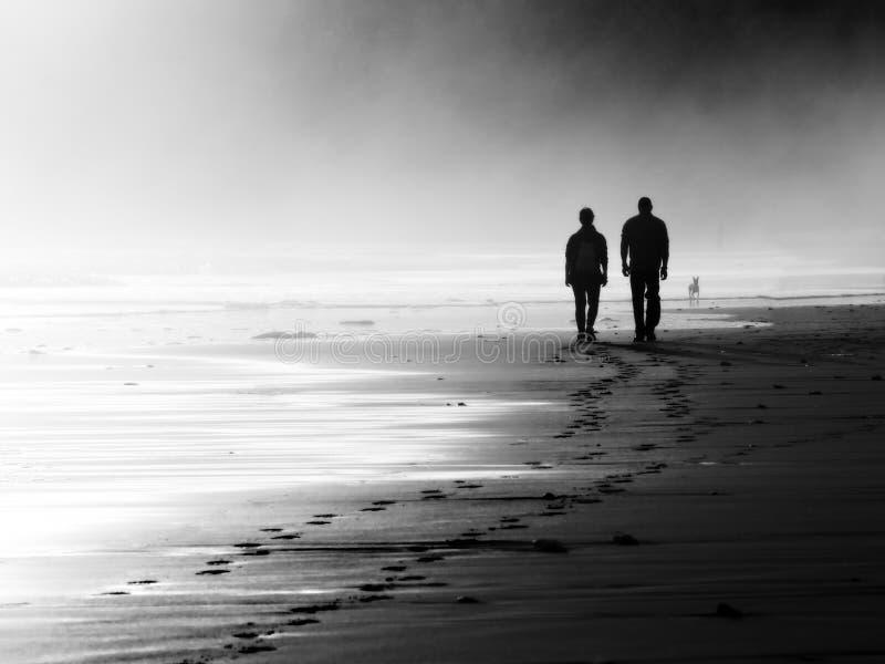 Ζεύγος που περπατά στην ομιχλώδη παραλία στοκ εικόνες