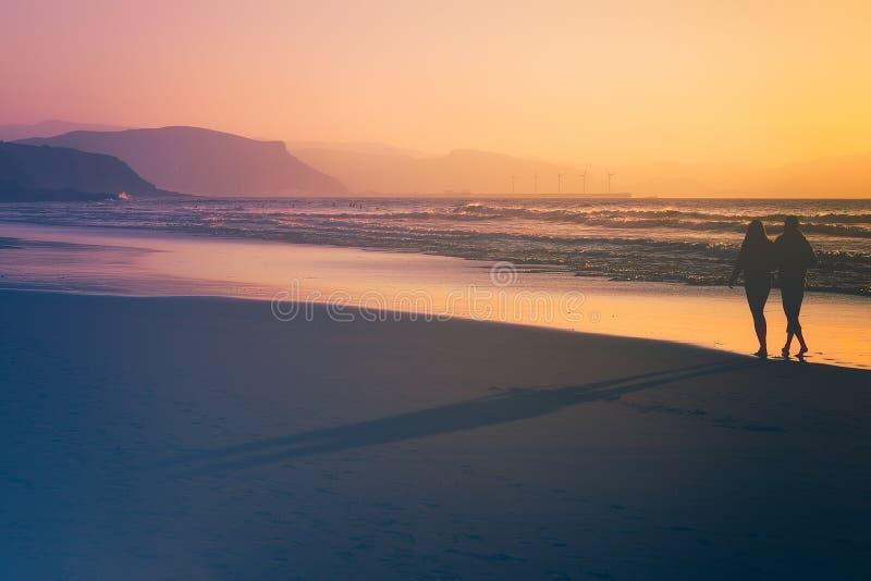 Ζεύγος που περπατά στην παραλία στο ηλιοβασίλεμα στοκ εικόνες