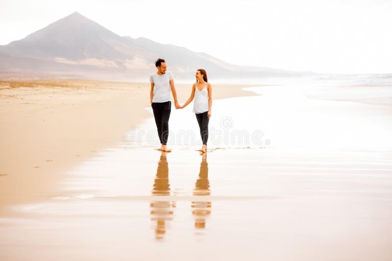 Ζεύγος που περπατά στην όμορφη παραλία στοκ εικόνα με δικαίωμα ελεύθερης χρήσης