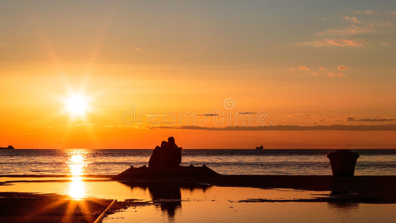 Ζεύγος που προσέχει ένα ρομαντικό ηλιοβασίλεμα στοκ φωτογραφίες