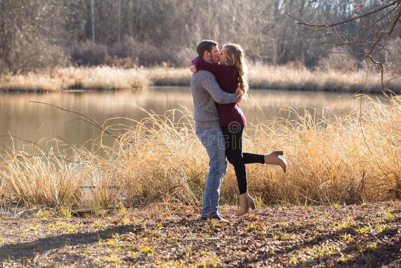 ζεύγος που στέκεται στη λίμνη που φιλά και που αγκαλιάζει η μια την άλλη στοκ εικόνα με δικαίωμα ελεύθερης χρήσης