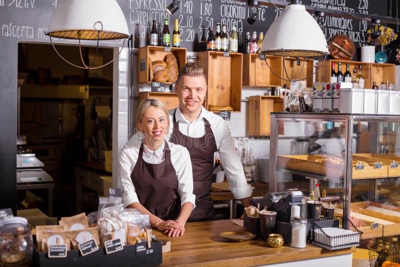 Ζεύγος που στέκεται στο νέο καφέ τους στοκ φωτογραφία