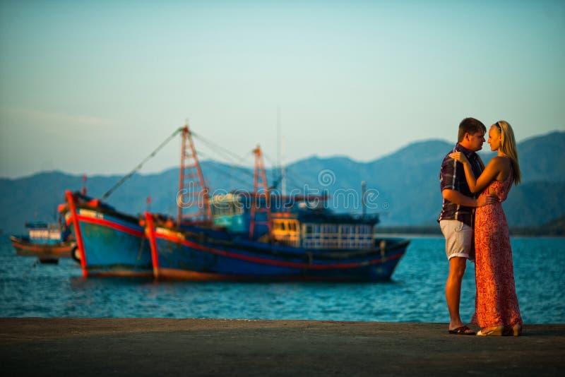 Ζεύγος που στέκεται στο υπόβαθρο της θάλασσας και των σκαφών στο ηλιοβασίλεμα στοκ εικόνες