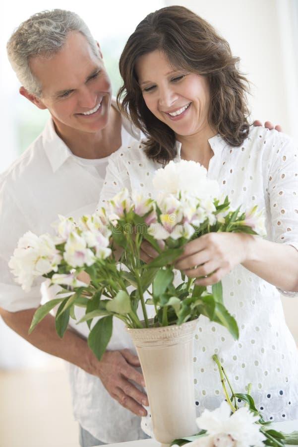 Ζεύγος που τακτοποιεί τα λουλούδια στο βάζο στοκ φωτογραφίες με δικαίωμα ελεύθερης χρήσης