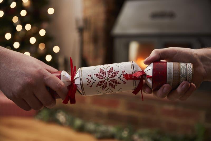 Ζεύγος που τραβά την κροτίδα στο δωμάτιο που διακοσμείται για τα Χριστούγεννα στοκ φωτογραφία με δικαίωμα ελεύθερης χρήσης