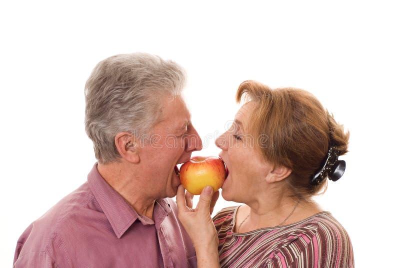 Ζεύγος που τρώει ένα μήλο σε μια άσπρη ανασκόπηση στοκ φωτογραφίες με δικαίωμα ελεύθερης χρήσης