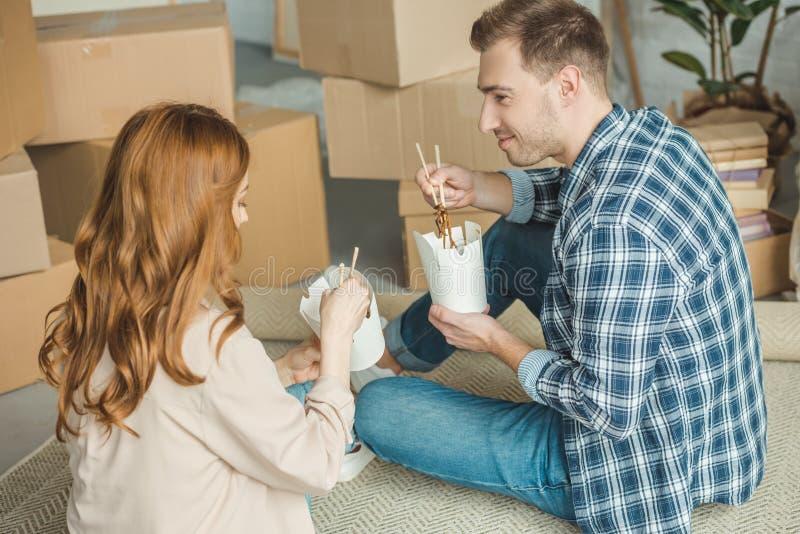 ζεύγος που τρώει τα ασιατικά τρόφιμα στο νέο διαμέρισμα με την κίνηση κουτιών από χαρτόνι στοκ εικόνες