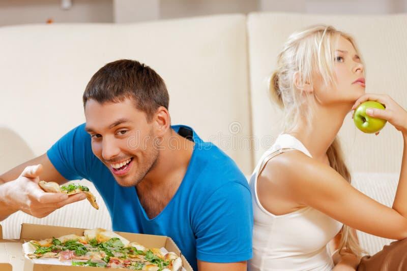 Ζεύγος που τρώει τα διαφορετικά τρόφιμα στοκ εικόνα με δικαίωμα ελεύθερης χρήσης