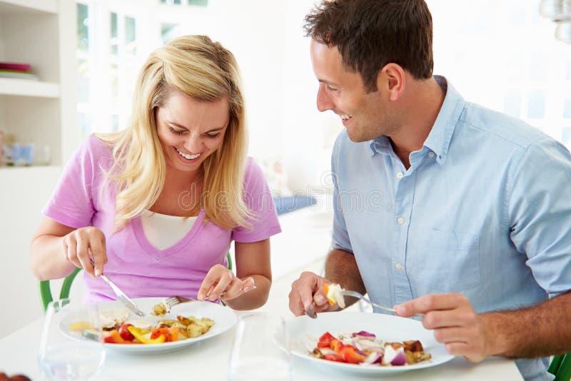 Ζεύγος που τρώει το γεύμα στο σπίτι από κοινού στοκ εικόνες
