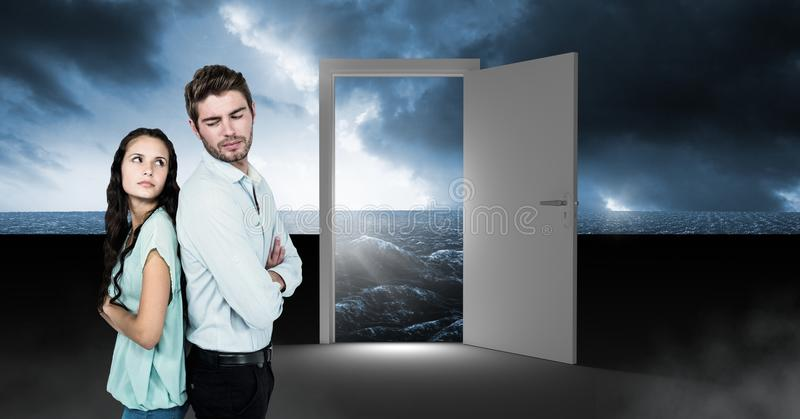 Ζεύγος που υπερασπίζεται τη ανοιχτή πόρτα με την υπερφυσική σκοτεινή πυράκτωση και τον ουρανό θάλασσας στοκ φωτογραφίες
