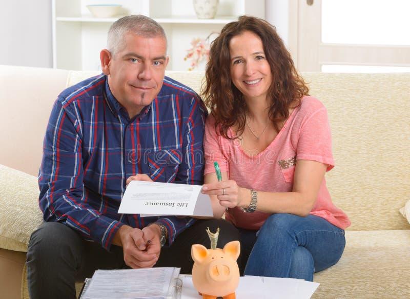 Ζεύγος που υπογράφει τη σύμβαση ασφαλείας ζωής στοκ φωτογραφίες με δικαίωμα ελεύθερης χρήσης