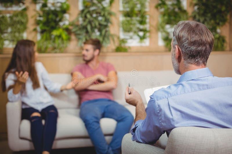 Ζεύγος που υποστηρίζει στη σύνοδο παροχής συμβουλών με έναν γιατρό στοκ φωτογραφίες