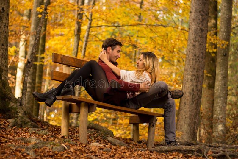 Ζεύγος που φαίνεται το ένα στο άλλο μάτια σε μια όμορφη συνεδρίαση πανοράματος/ζεύγους φθινοπώρου σε μια τράπεζα στο δάσος φθινοπ στοκ φωτογραφία