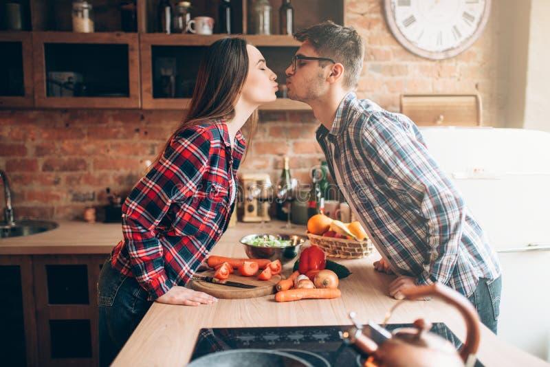 Ζεύγος που φιλά προετοιμάζοντας ένα ρομαντικό γεύμα στοκ φωτογραφίες