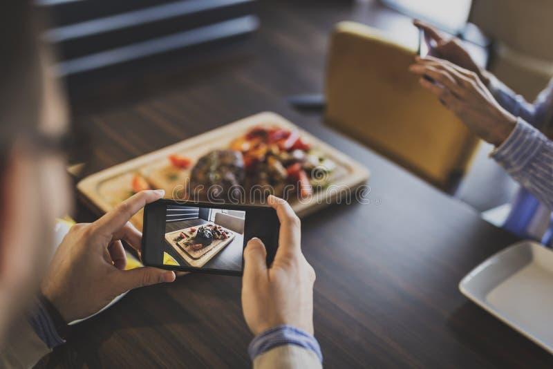 Ζεύγος που φωτογραφίζει τα τρόφιμα σε ένα εστιατόριο στοκ φωτογραφίες με δικαίωμα ελεύθερης χρήσης