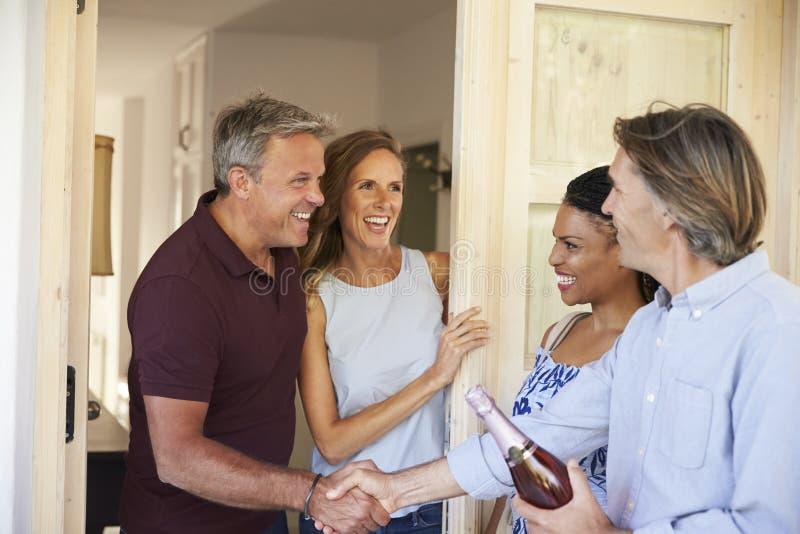 Ζεύγος που χαιρετά τους φιλοξενουμένους τους στην πόρτα του σπιτιού τους στοκ εικόνες