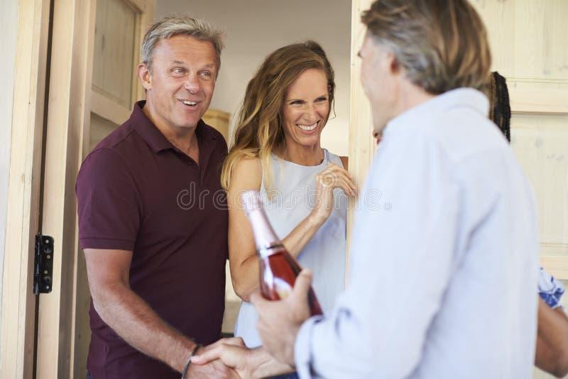 Ζεύγος που χαιρετά τους φιλοξενουμένους τους στην πόρτα του σπιτιού τους στοκ εικόνα