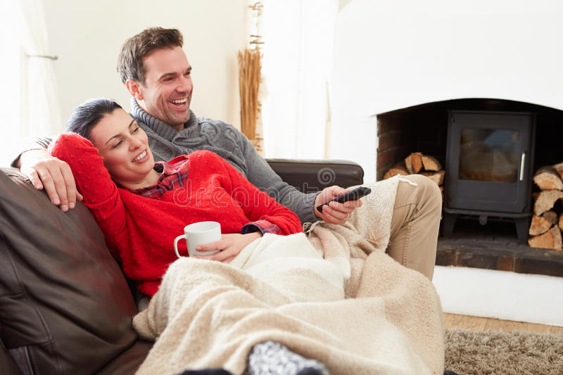 Ζεύγος που χαλαρώνει την τηλεόραση στο σπίτι προσοχής στοκ φωτογραφία με δικαίωμα ελεύθερης χρήσης