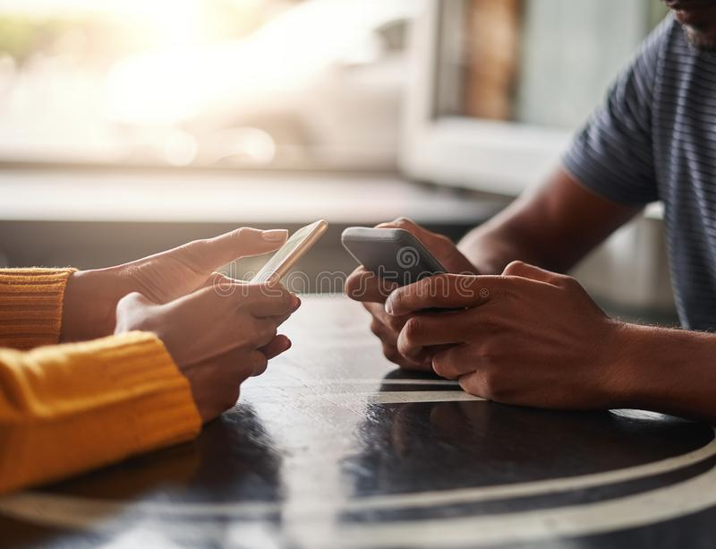 Ζεύγος που χρησιμοποιεί τα κινητά τηλέφωνά τους στον καφέ στοκ εικόνα