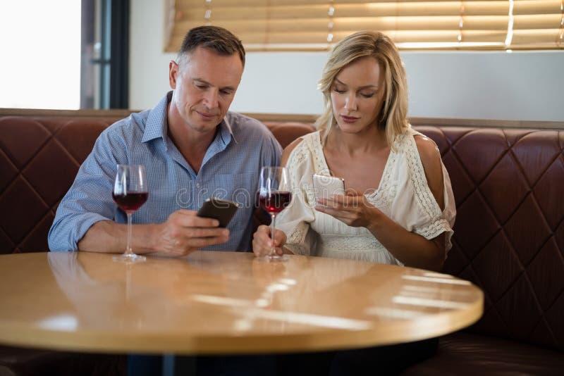 Ζεύγος που χρησιμοποιεί τα κινητά τηλέφωνα ενώ έχοντας το ποτήρι του κρασιού στοκ φωτογραφίες