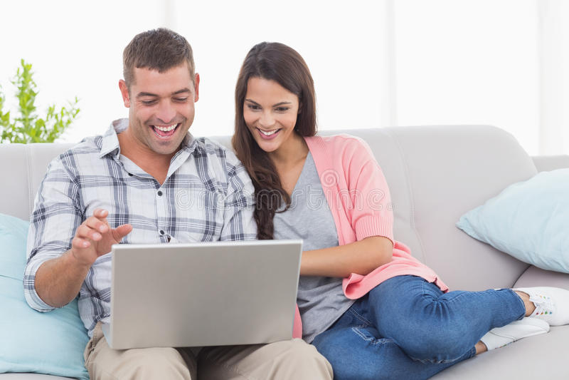 Ζεύγος που χρησιμοποιεί το lap-top για την τηλεδιάσκεψη στον καναπέ στοκ εικόνα