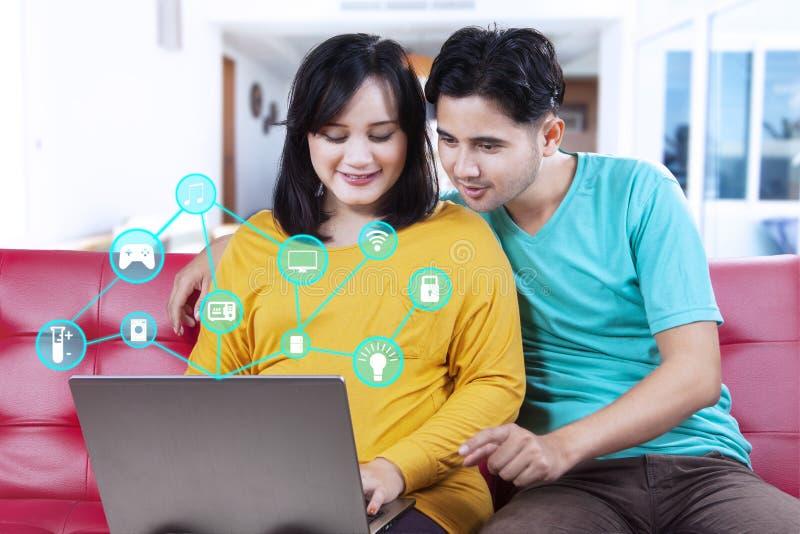 Ζεύγος που χρησιμοποιεί το lap-top με το έξυπνο εγχώριο σύστημα στοκ εικόνα