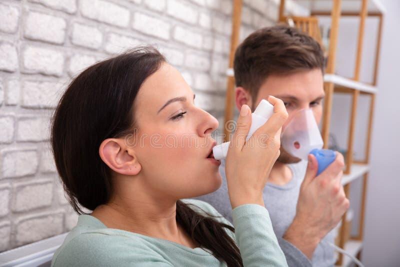 Ζεύγος που χρησιμοποιεί Inhaler άσθματος στοκ εικόνα με δικαίωμα ελεύθερης χρήσης
