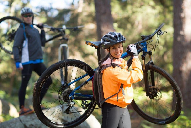 Ζεύγος ποδηλατών που κρατά το ποδήλατο βουνών τους και που περπατά στο δάσος στοκ φωτογραφίες